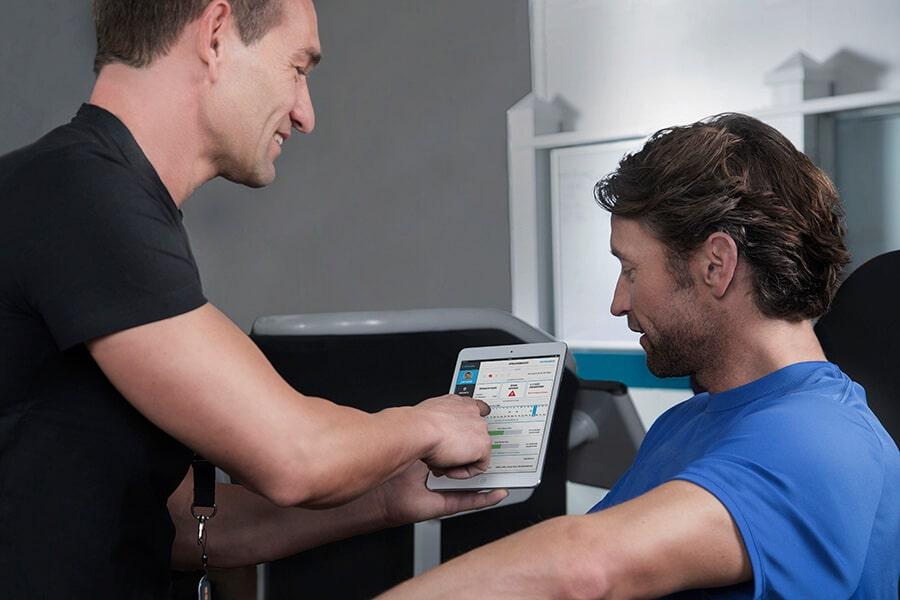 Trainer erklärt Mann die Apps für den eGym Zirkel