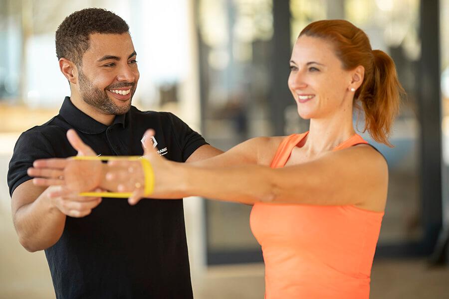 Frau mit Personal Trainer beim Rehasport im Fitnessstudio Darmstadt