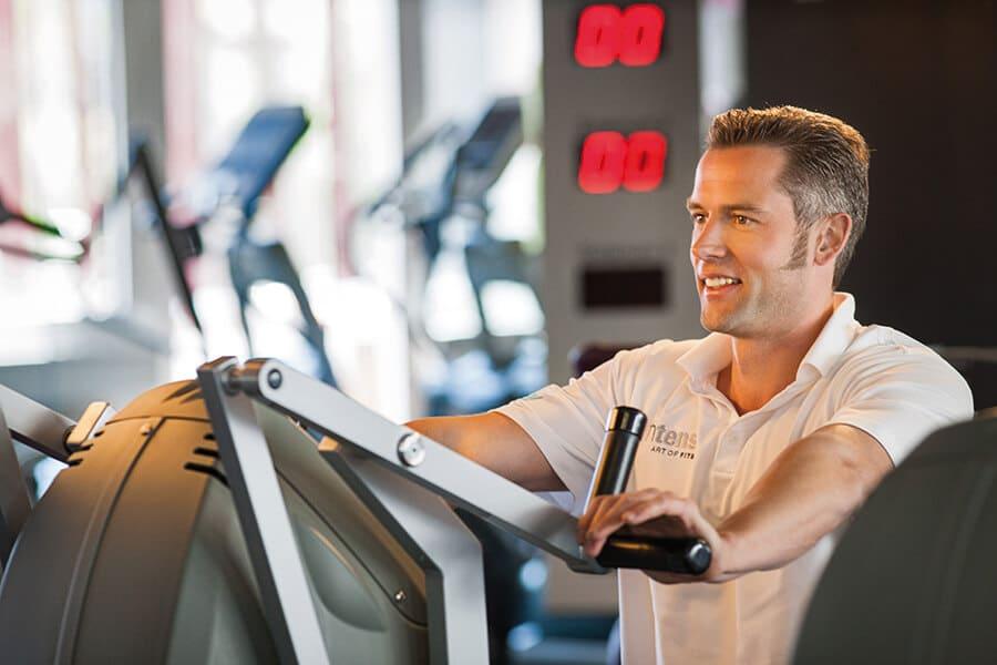 Mann beim Gerätetraining im Mann beim Training an den Geraeten im Body Culture Fitnessstudio